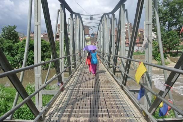 Crossing a bridge by the Monkey Temple--everyone carried umbrellas in the valley for all the sun.