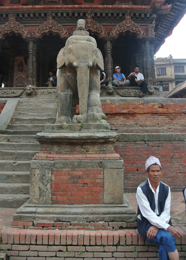 a Nepali man sitting by an elephant statue in Bhanktapur's Durbar Square